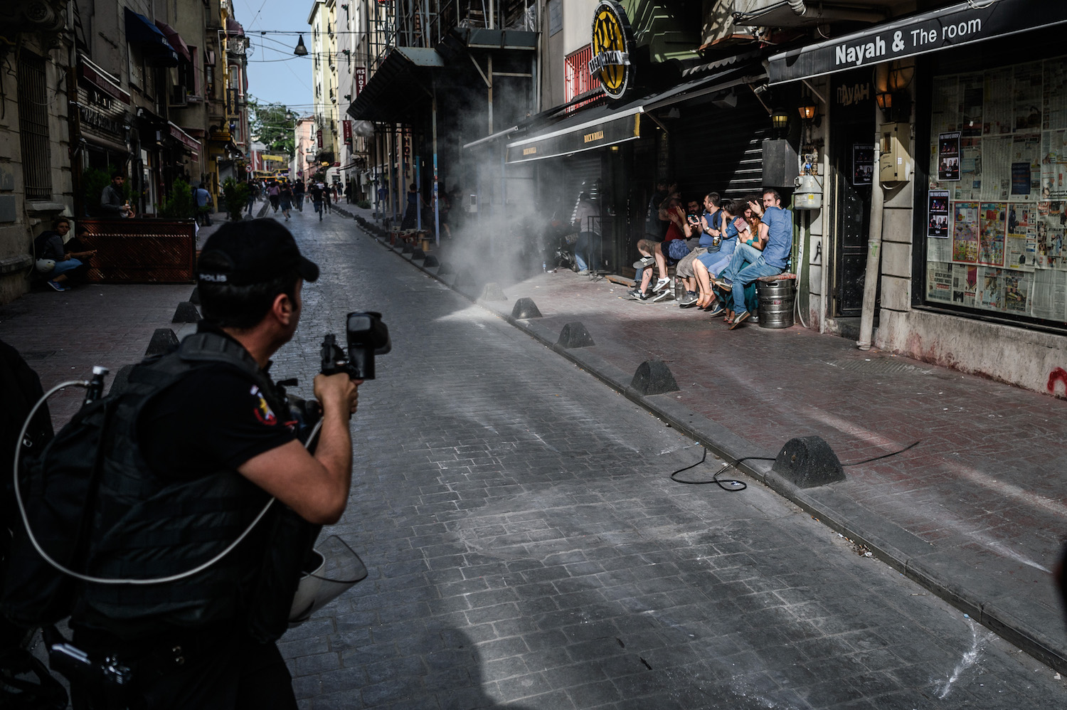 "Turkish anti-riot police officers fire rubber bullets to disperse demonstrators gathered for a rally staged by the LGBT community on Istiklal avenue in Istanbul on June 19, 2016. Turkish riot police fired rubber bullets and tear gas to break up a rally staged by the LGBT community in Istanbul on June 19 in defiance of a ban. Several hundred police surrounded the main Taksim Square -- where all demonstrations have been banned since 2013 -- to prevent the ""Trans Pride"" event taking place during Ramadan. / AFP / OZAN KOSE (Photo credit should read OZAN KOSE/AFP/Getty Images)"