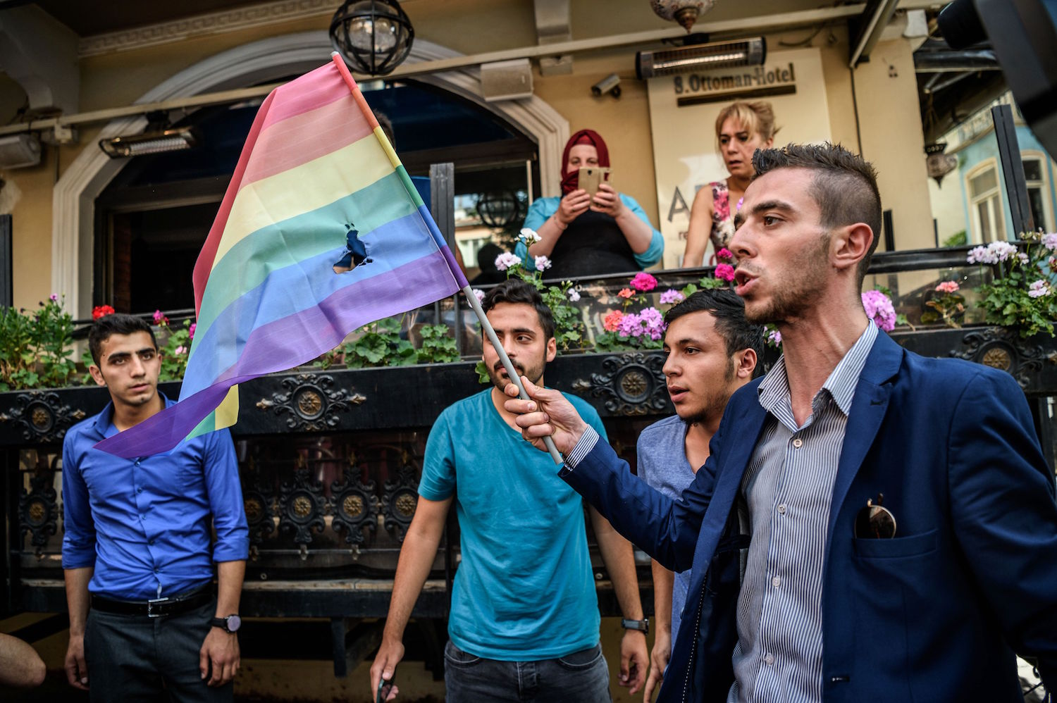 """Turkish nationalists burn a rainbow flag during a rally staged by the LGBT community on Istiklal avenue in Istanbul on June 19, 2016. Turkish riot police fired rubber bullets and tear gas to break up a rally staged by the LGBT community in Istanbul on June 19 in defiance of a ban. Several hundred police surrounded the main Taksim Square -- where all demonstrations have been banned since 2013 -- to prevent the """"Trans Pride"""" event taking place during Ramadan.  / AFP / OZAN KOSE        (Photo credit should read OZAN KOSE/AFP/Getty Images)"""