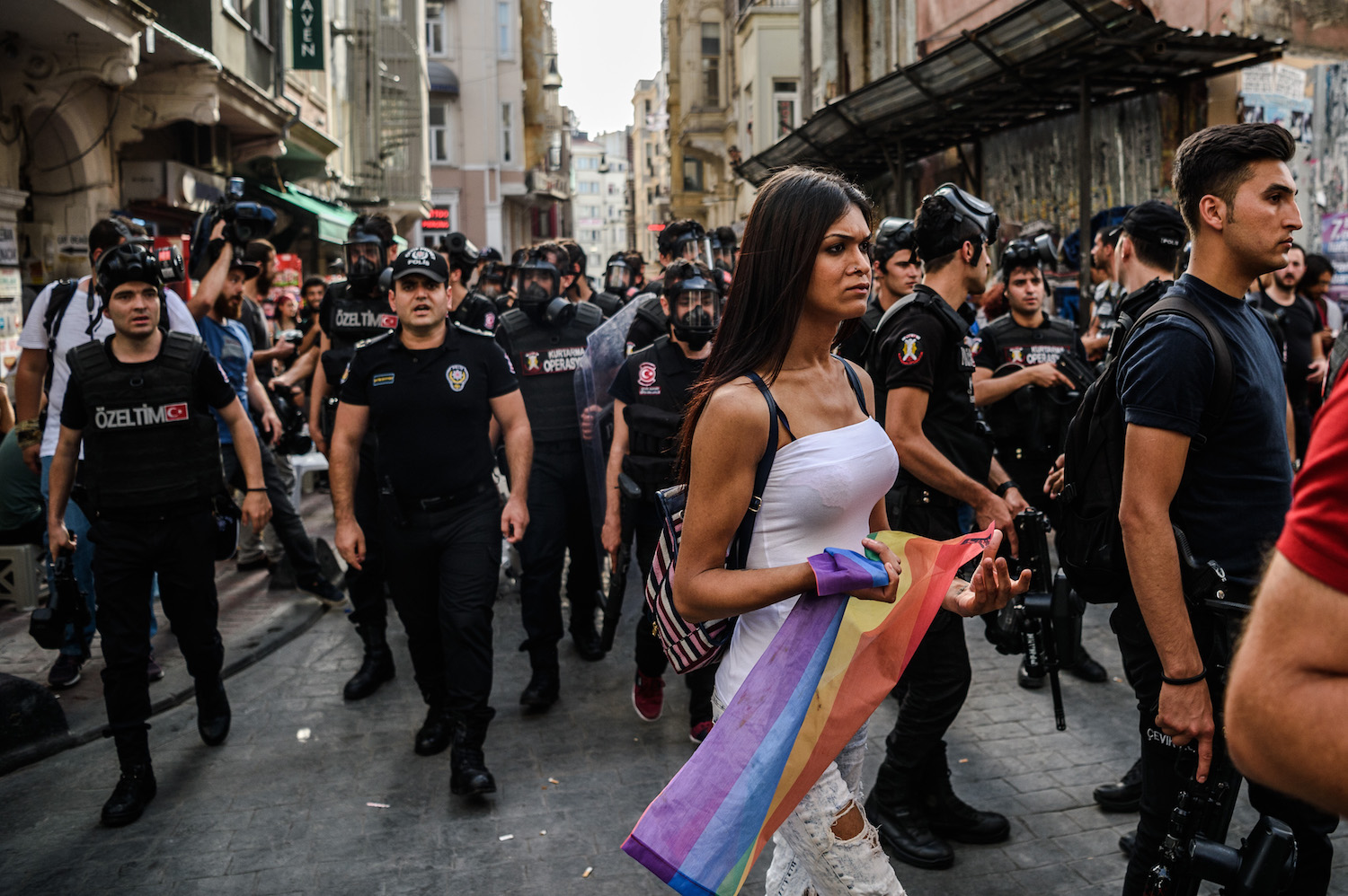 "A woman holds a rainbow flag as Turkish anti-riot police officers disperse demonstrators gathered for a rally staged by the LGBT community on Istiklal avenue in Istanbul on June 19, 2016. Turkish riot police fired rubber bullets and tear gas to break up a rally staged by the LGBT community in Istanbul on June 19 in defiance of a ban. Several hundred police surrounded the main Taksim Square -- where all demonstrations have been banned since 2013 -- to prevent the ""Trans Pride"" event taking place during Ramadan. / AFP / OZAN KOSE (Photo credit should read OZAN KOSE/AFP/Getty Images)"