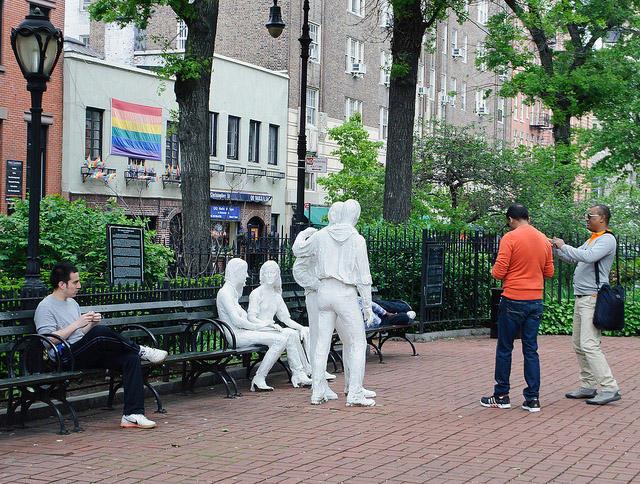 A parkban egy szobor emlékezik meg a Stonewall-lázadásról. Háttérben a Stonewall Inn. Fotó: INSAPPHOWETRUST / FLICKR